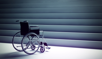 Empty manual wheelchair sits at the bottom of a set of stairs. The photo is styled in mostly gray and looks slightly ominous.