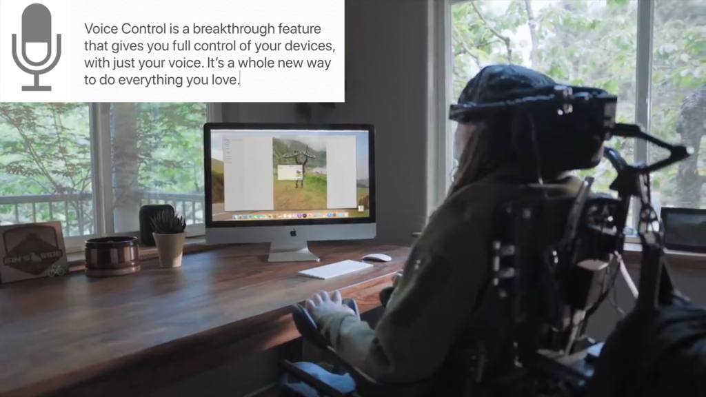 "Power wheelchair user with head and hand rests sits at desk in front of iMac desktop monitor, keyboard, and mouse with minimal desk décor. Overlaid on the photo is the Mac microphone icon and text from the original video: ""Voice Control is a breakthrough feature that gives you full control of your devices, with just your voice. Its a whole new way to do everything you love."""