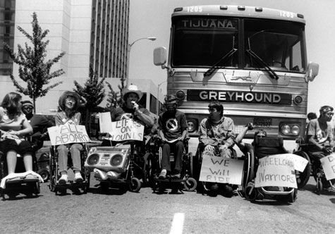 """Diverse group of mobility-impaired protesters with signs such as """"All board"""" and """"We will ride"""" seated in front of Greyhound bus on city street."""